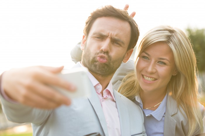 Playful business couple taking selfie outdoors on sunny day